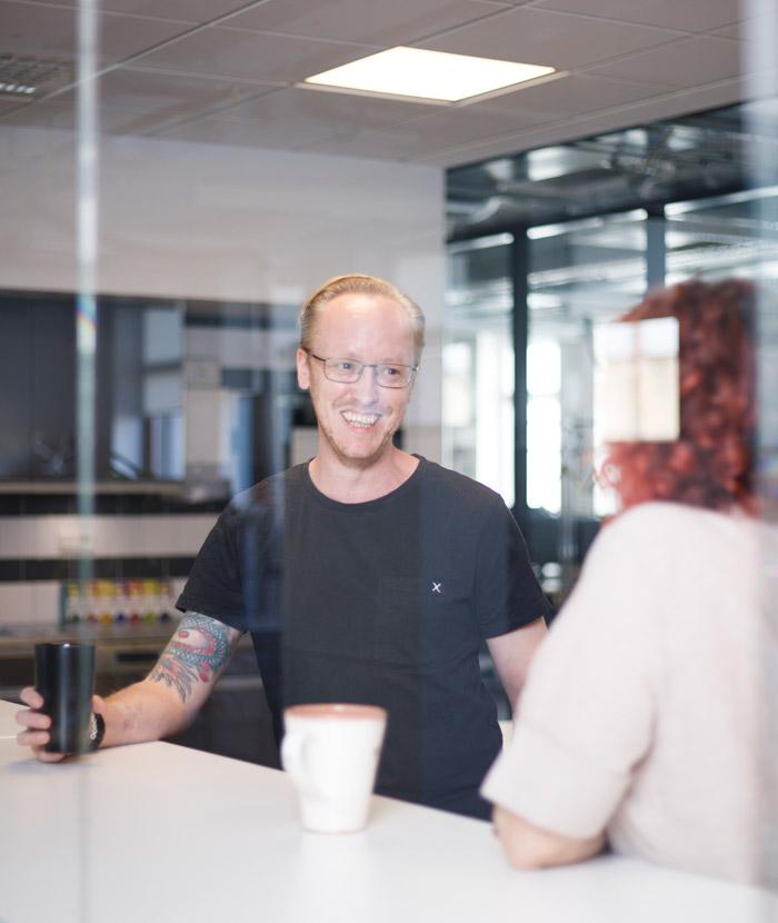 Glad medarbetare i samtal med kollega över en varm kopp dryck