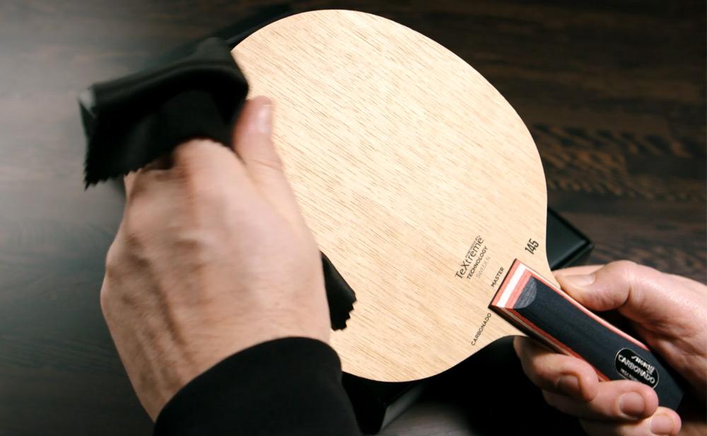 Person putsar trägrunden till ett bordtennisrack